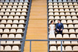 Beautiful bride and groom sitting on football stadium stand on wedding day